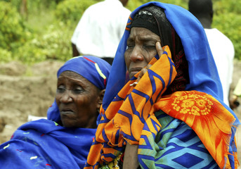 Women grieve at the scene of a plane crash in the Nigerian capital Abuja