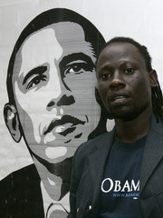 Kenyan musician Makadem poses in front of a poster of U.S. Democratic presidential nominee Obama after launching a music video in Nairobi