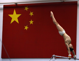 Young male gymnast practises in front of a Chinese flag at a gymnastic hall in the Shichahai sports school in Beijing