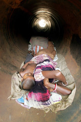 A homeless Indian woman and her child sleep inside a drain pipe on a hot summer day in the eastern I..