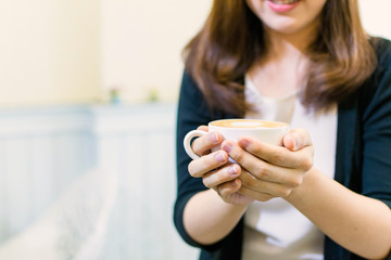 Woman holding coffee cup for serving.