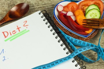 Treatment of obesity. Diet on a wooden table. Healthy vegetables.
