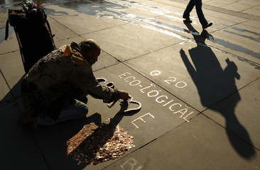 A demonstrator makes an anti-G20 sign out of coins at Trafalgar Square in London