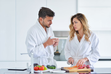 Happy couple cooking breakfast together in the kitchen