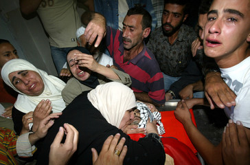 Palestinians mourn over the body of one of three Fatah millitant in Nablus.