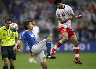 Japan's Kengo Nakamura and Bahrain's Mahmood Abdulrahman fight for the ball during their 2010 FIFA World Cup qualifier soccer match in Saitama, Japan