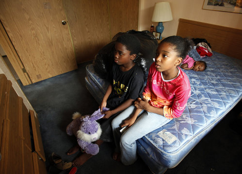 Javonte Miles and his sister, Kayla, watch tv on the bed in the motel room the family is living in as their eleven month old cousin, Bradley, naps in Grand Prairie