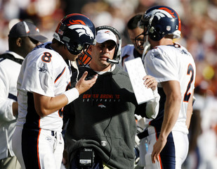Denver Broncos head coach McDaniels talks to his starting quarterback Orton and back up quarterback Simms in the first half of their NFL football game against the Washington Redskins in Landover