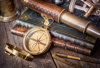 Wall Mural - Exploration and nautical theme grunge background. Compass, telescope, sextant, divider and old book on wood desk.