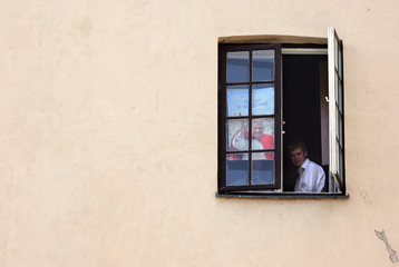 A young Polish believer sits in the window near the St John's Cathedral