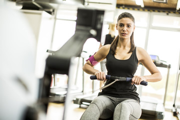 Young woman exercises on an exercise machine at the gym listening to music