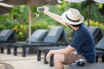 Young Asian happy man taking a selfie shot on smartphone at resort, vacation time and summer holiday travel concepts, relaxation mode