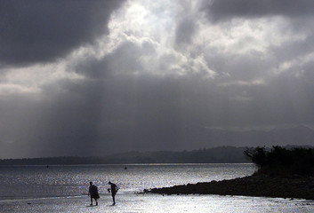 An afternoon storm looms above fishermen on the mud flats of a Suva beach September 9, 2001. [Fiji's..