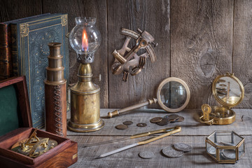 Wall Mural - Exploration and nautical theme grunge background. Compass, telescope, sextant, coin, divider and old book on wood desk.