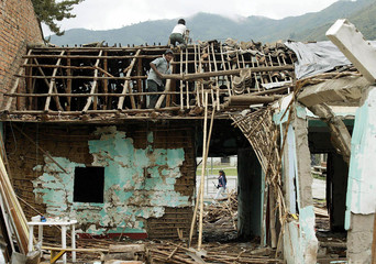 Colombian peasants work in their house destroyed by combats in Toribio.