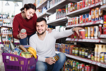Smiling family couple purchasing tinned food