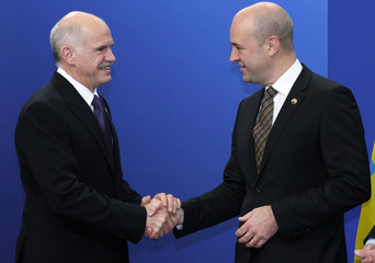 Greece's Prime Minister Papandreou shakes hands with Sweden's Prime Minister Reinfeld in Brussels