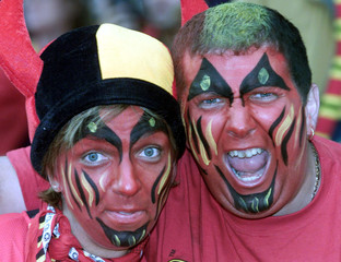 Belgium fans with their faces painted in red and wearing devil's horns sing and shout prior to their..