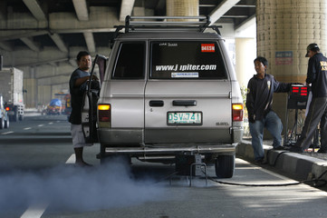 Filipino traffic enforcers hook up vehicle with a device that measures its smoke-belching levels along a busy street in Manila
