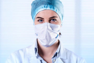 Female Surgeon wearing White Coat, cap and mask