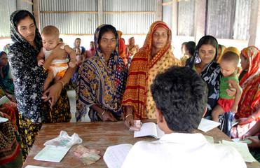 Woman queues to return bank loan instalment in village of Basta