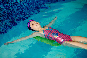 Little girl learning to swim with board in sport pool. Swimming school for small children. Healthy kid enjoying active lifestyle.