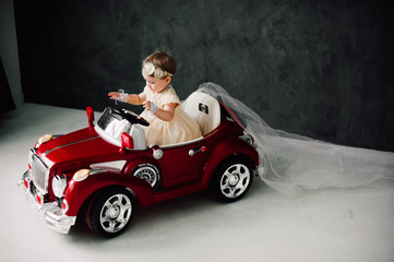 two babies wedding - girl dressed as bride playing with toy car