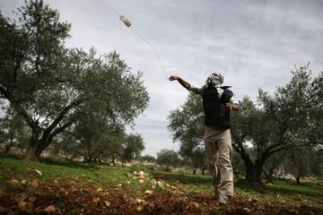 A Palestinian demonstrator throws a stone at Israeli border policemen in Bilin