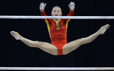 He of China performs her routine on the uneven bars during the qualifying round of the Gymnastics World Championships at the O2 Arena in London