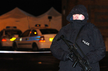 AN ARMED POLICE OFFICE GUARDS THE SCENE WHERE TWO POLICE OFFICERS WERE SHOT IN LEEDS.