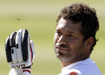 India's Tendulkar brushes a wasp away during a training session for their third international test cricket match against New Zealand in Wellington