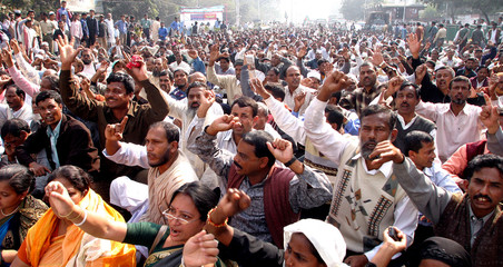 Non-government primary school teachers in funeral clothes chant slogans during a protest in Dhaka