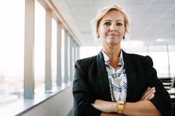 Confident mature businesswoman standing in office