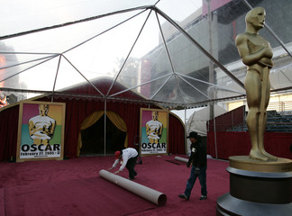 Workers roll a piece red carpet near an Oscar statue under clear rain tents at the arrivals area near ...