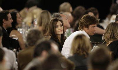 Actors Angelina Jolie and Brad Pitt arrive at their table during the 2008 Film Independent's Spirit Awards in Santa Monica, California