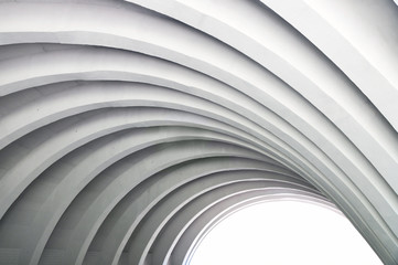 Architectural background. Modern white concrete arched ceiling in perspective. The same semicircular shape. The light in the end.