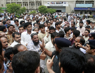 Protesting investors argue with the police at the Karachi Stock Exchange