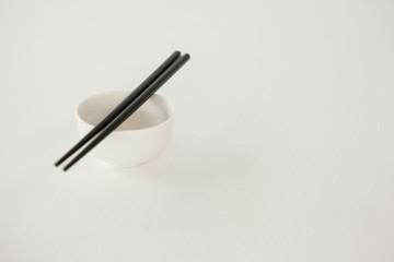 Pair of chopsticks over a bowl
