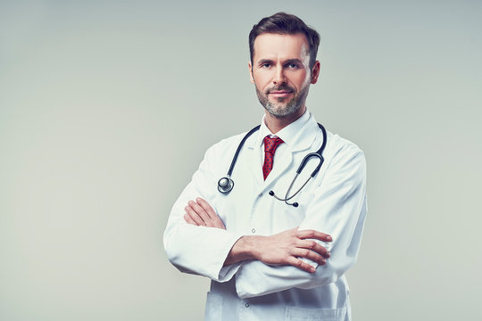 Portrait of handsome doctor standing with crossed arms. Isolated