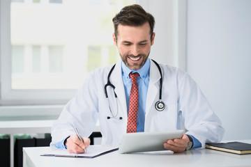 Happy doctor writing prescription