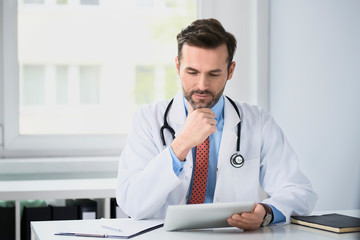 Doctor working at his office with digital tablet