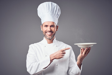 Smiling chef holding plate and pointing on it. Isolated