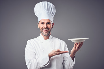 Happy chef holding plate