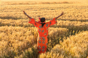 African woman in traditional clothes arms raised in field of crops at sunset or sunrise