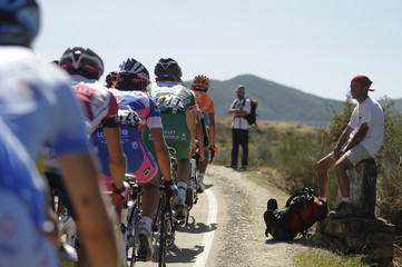 "Riders cycle past pilgrims during the 16th stage of the Tour of Spain ""La Vuelta"" cycling race from Ponferrada to Zamora"