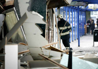 Firefighter looks inside a destroyed shop after a gas explosion in a shopping centre in Utrecht
