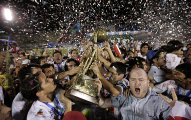 Gustavo Morinigo of Nacional celebrates with the trophy after winning the Paraguayan First Division Championship 2009 against Olimpia in Asuncion