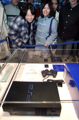 Japanese visitors look at a glass-encased PlayStation 2 video game console on display at PlayStation..