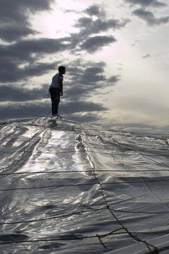 A worker puts a plastic sheet over the top of a greenhouse under-construction in El Ejido