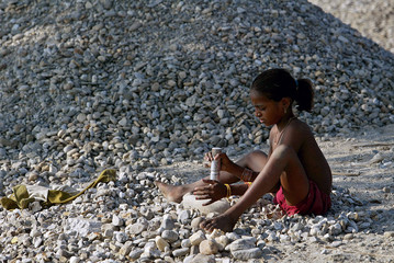 Khatun, nine-year-old child labourer, breaks stones on bank of river Balason on outskirts of northeastern city of Siliguri